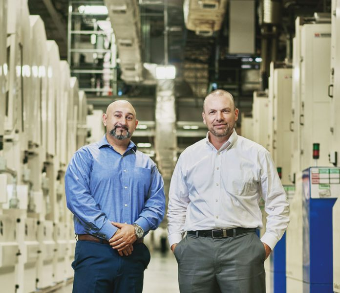 Hector Elias and Rob Anderson of IGT standing between the Tresu and Gallus flexo presses – each press has more than 20 print units. Photo IGT