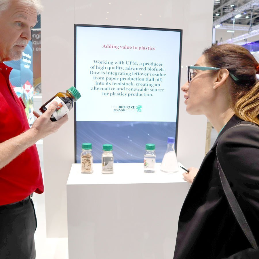 Shaun Parkinson explains to a plastics business woman at the Dow stand at K, how polyethylene can be produced as a by-product of the paper making and pulping process which uses wood chips. Photo PSA