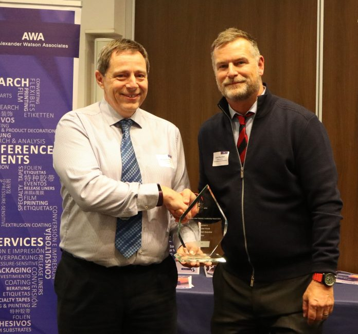 Alex Knott, Dow (left), receives the AWA Release Liner Industry Leadership Award from Corey Reardon, AWA Alexander Watson Associates